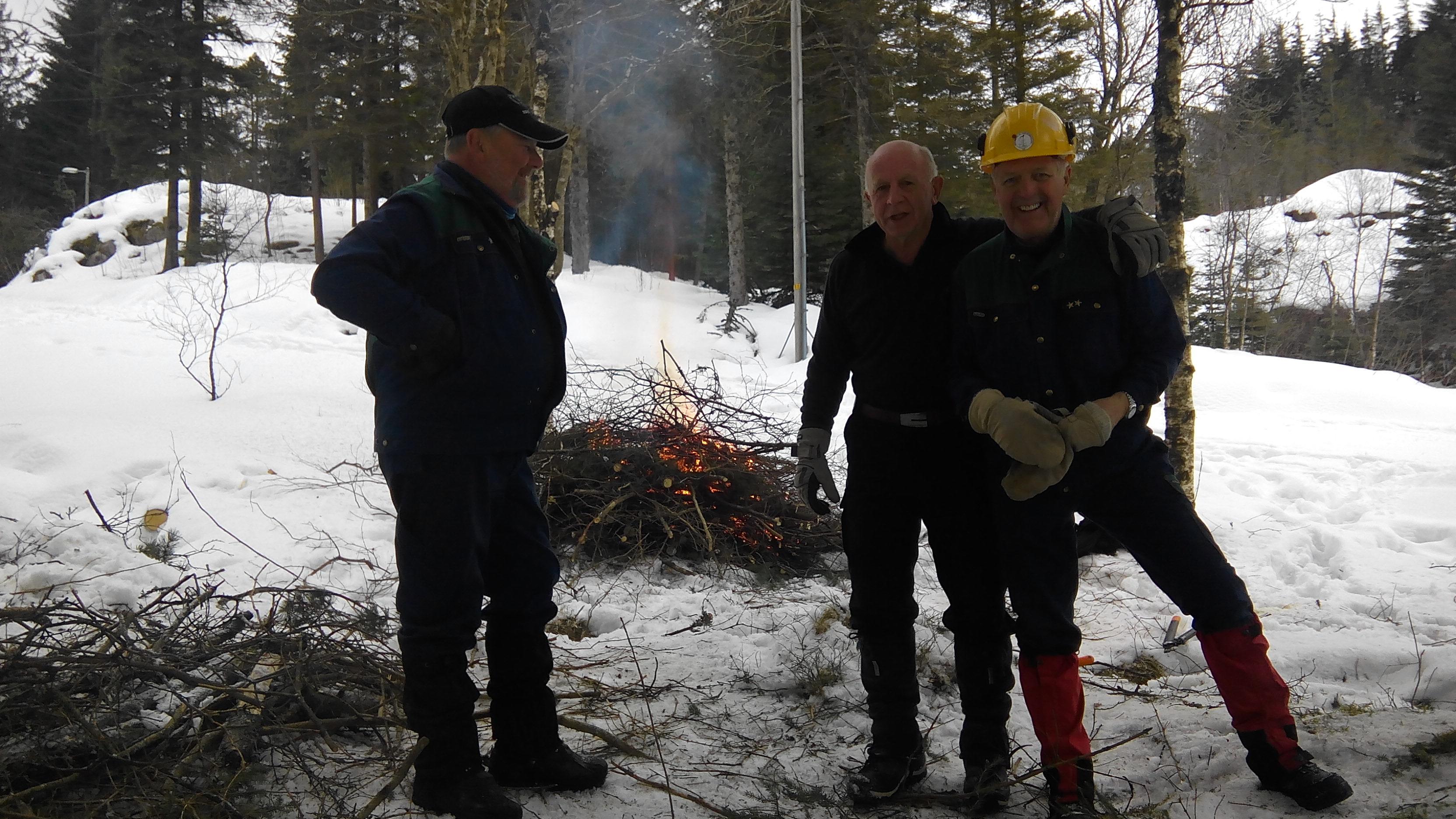 101  Tre karer som holder varmen ved bålet.