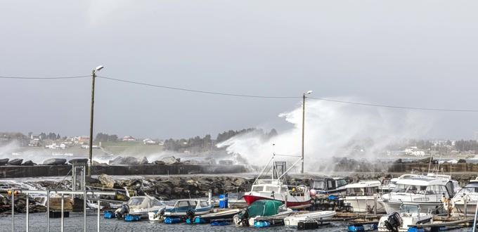 Viser sjøen slå over moloen midt på dagen under stormen i april 2020.
